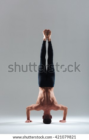 Man doing headstand isolated on a white background - stock photo