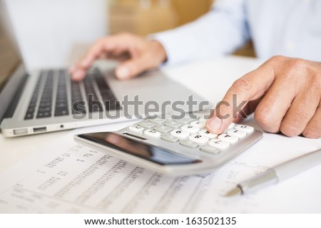 Man doing his accounting, financial adviser working - stock photo