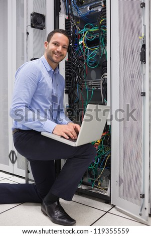 Man doing maintenance at the data store with laptop - stock photo