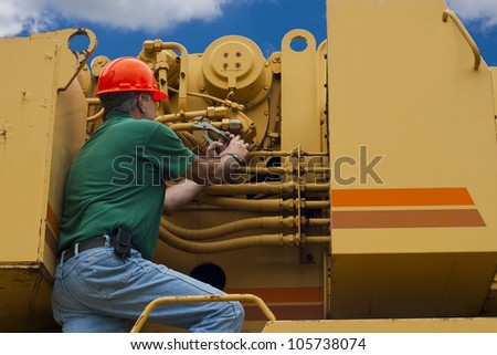 man doing maintenance work on a large piece of machinery