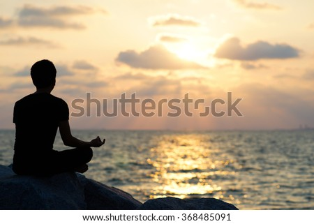 Man doing meditation sitting on the rock, Beautiful Sunset by the sea.