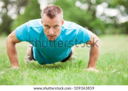 Man doing press ups outdoors - stock photo