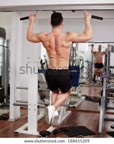 Man doing pull-ups in the gym, view from the back - stock photo