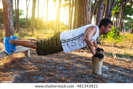 man doing push up in a pine forest at sunset