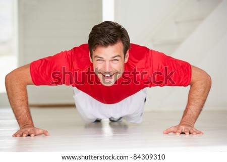 Man doing push-ups in home gym - stock photo