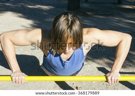 Man doing push-ups on a bar - stock photo