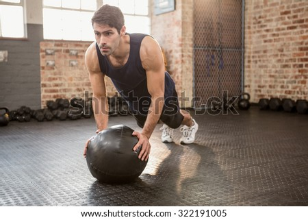 Man doing push ups on medicine ball at the gym - stock photo