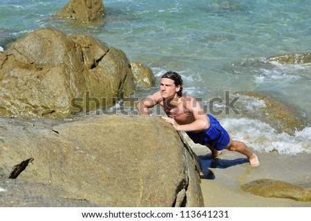 man doing push ups on the beach