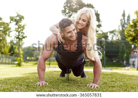 Man doing push-ups with woman on back, healthy couple, workout with own body weight, outdoor - stock photo