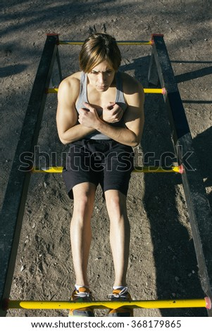 Man doing sit ups sitting on a bar  - stock photo