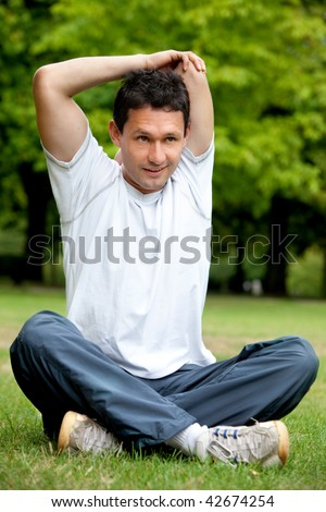Man doing stretching exercise for her arms and back at the park
