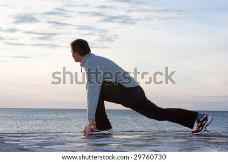 Man doing stretching exercises at the sea - stock photo