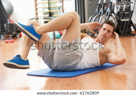 Man Doing Stretching Exercises In Gym - stock photo