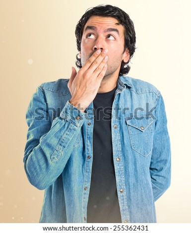 Man doing surprise gesture over ocher background - stock photo