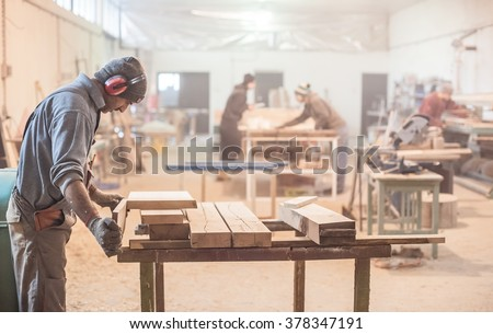 Man doing woodwork in carpentry. Carpenter work on wood plank in workshop - stock photo