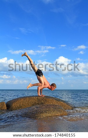 Man doing yoga by the beach at morning sunlight