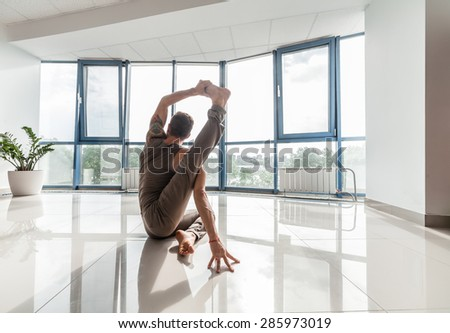 Man Doing Yoga Exercise On The Reflection Floor At The Studio In Front Of A  Big