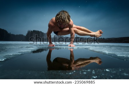 Man doing yoga exercise (parsva bakasana) on the ice of frozen lake - stock photo