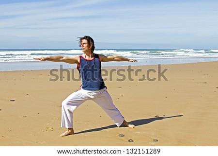 Man doing yoga exercises at the beach - stock photo