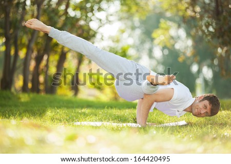 Man doing yoga exercises in the park - stock photo
