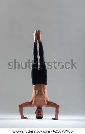 Man doing yoga headstand isolated on a white background - stock photo