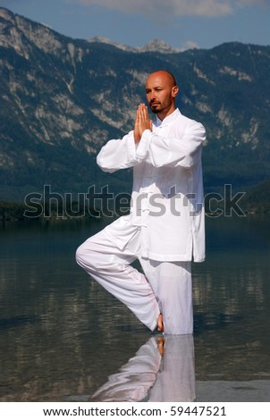 Man doing yoga in fresh mountain lake water
