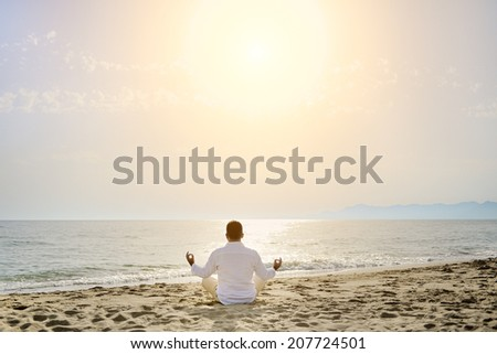 man doing yoga meditation exercises on the beach at sunset- healthy lifestyle concept - stock photo