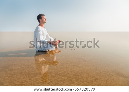 Man doing yoga meditation in Lotus position sitting in the sea water