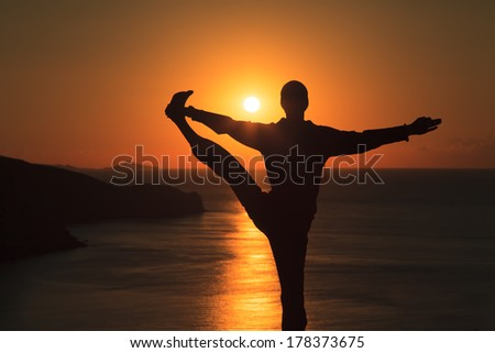 Man doing yoga on the beach at sunset - stock photo
