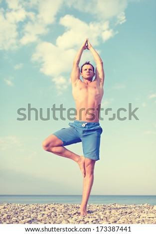 man doing yoga on the beach in the summer on the nature - stock photo