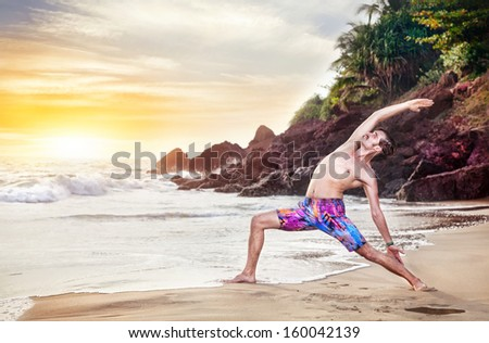 Man doing yoga on the beach near the ocean at sunset in India - stock photo