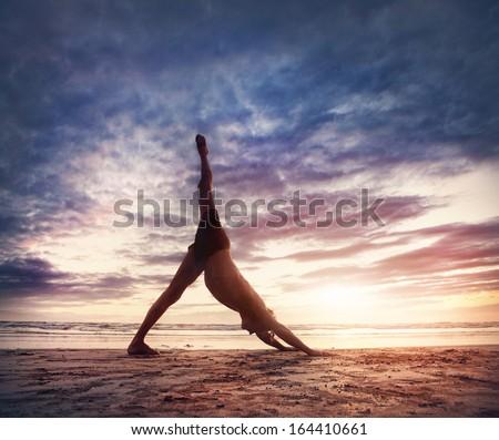 Man doing Yoga on the beach near the ocean in India - stock photo
