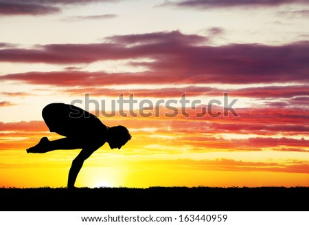 Man doing Yoga on the grass at sunset sky - stock photo