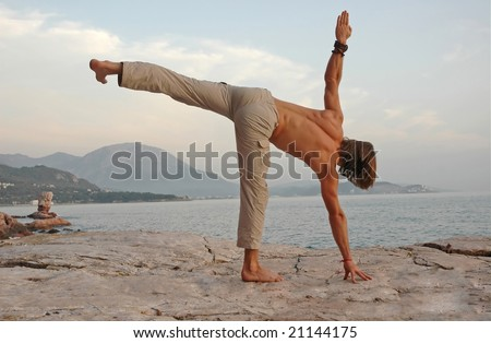 Man doing yoga outdoors. Ardha-Chandrasana. Side view. - stock photo