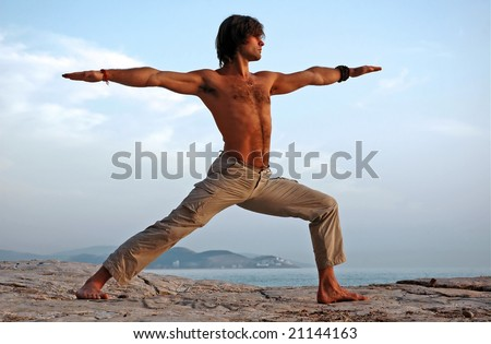 Man doing yoga outdoors. Virabhadrasana. Side view.