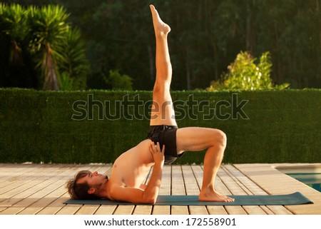 Man doing yoga outside. - stock photo