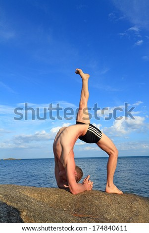 Man doing yoga Wheel pose by the beach at morning sunlight