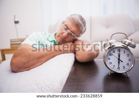 Man dozing on the couch beside alarm clock at home in the living room