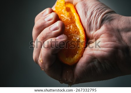 man dramatic squeezes orange. Concept squeezed a man  is tired from work. - stock photo