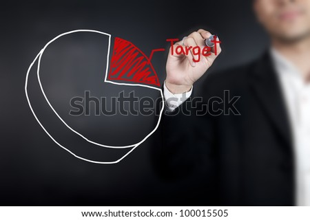 Man drawing a pie chart on whiteboard - stock photo