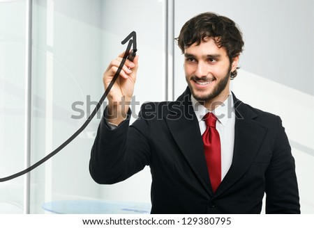 Man drawing a rising arrow on the glass - stock photo