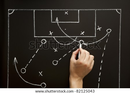 Man drawing a soccer game strategy with white chalk on a blackboard. - stock photo