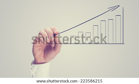 Man drawing an ascending bar graph on a virtual interface conceptual of analysis, performance growth and planning, vintage effect with copyspace. - stock photo