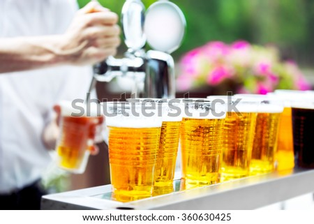 Man drawing beer from tap in an plastic cup. Draught beer. The bartender pours a beer in a plastic cup. On the bar table are plastic cups with a beer - stock photo