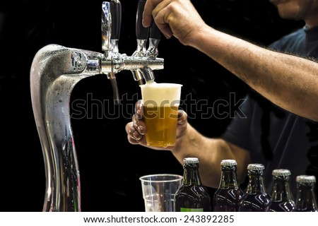 Man drawing beer from tap in an plastic cup. Isolated in a black background  - stock photo