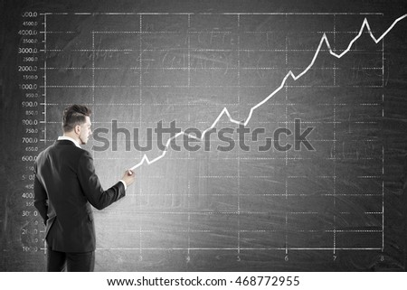 Man drawing graph on large blackboard. Concept of successful business strategy and income growth in corporation.