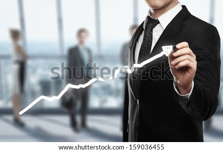 man drawing graph on office background - stock photo