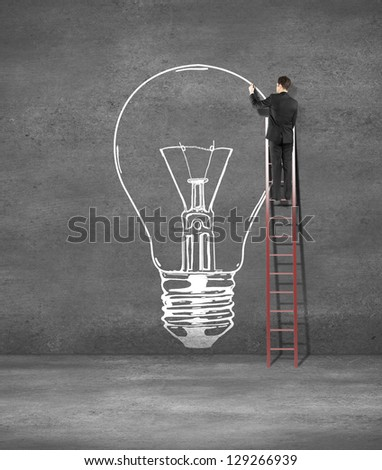 man drawing lamp on concrete wall - stock photo