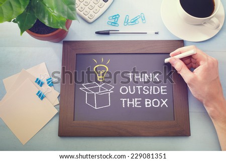 Man drawing Think Outside the Box with idea light bulb on a little blackboard - stock photo