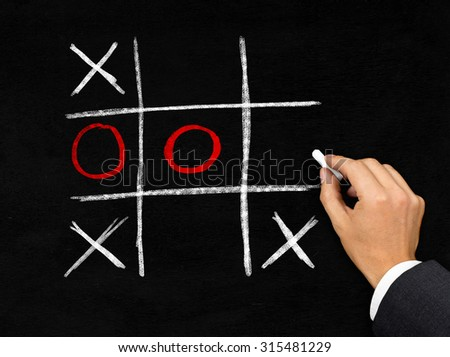 Man drawing tic-tac-toe game with chalk on blackboard background